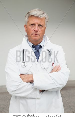 Serious doctor with folded arms in labcoat