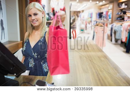 Woman  reaching  bag behind the counter and smiling