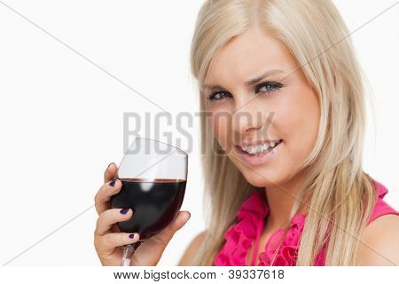 Smiling blonde drinking a glass of wine against white background