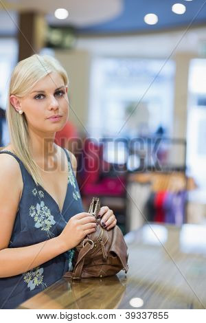 Woman holding handbag at counter in clothing store