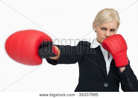 Blonde businesswoman with red gloves fighting against white background