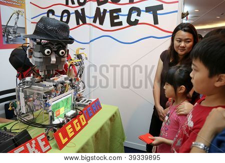 SUBANG JAYA - NOVEMBER 10: Unidentified visitors watch a robot interact with them at the World Robot Olympaid on Nov 10, 2012 in Subang Jaya, Malaysia. This year's theme is robots connecting people.