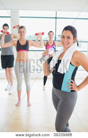 Smiling woman at front of aerobics class with water and towel