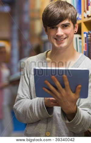 Man with tablet pc beside bookshelf in college library