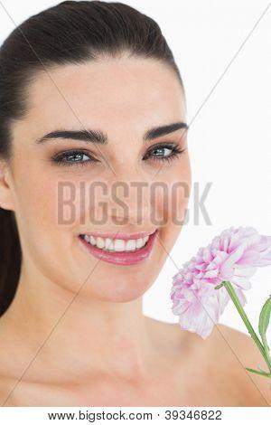 Pálida mulher mostrando uma flor enquanto sorrindo