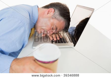 Exhausted man holding coffee and sleeping on his laptop on his desk in a white background