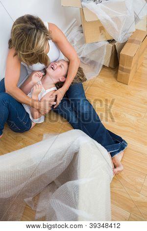Mother tickling her daughter on the floor