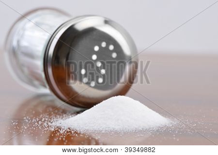 Salt spilling on table from salt cellar
