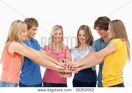 A group of friends with their hands stacked on top of each other as they look at the stack