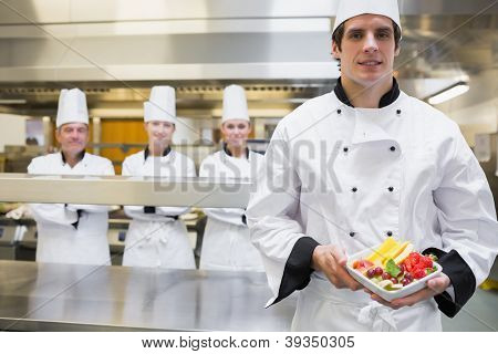 Chef holding fruit salad with team standing behind him in kitchen