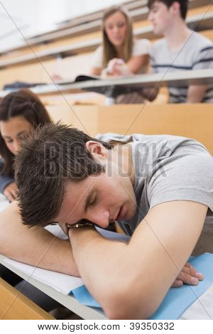 Student sleeping at the lecture hall leaning on table