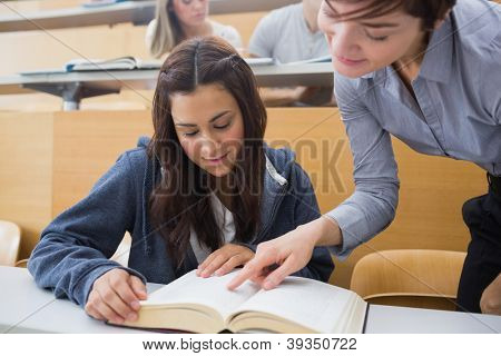 Teacher and student looking at a book at the lecture hall