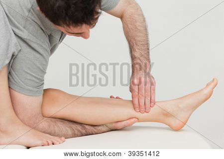 Serious osteopath massaging the shin bone of a patient in a room