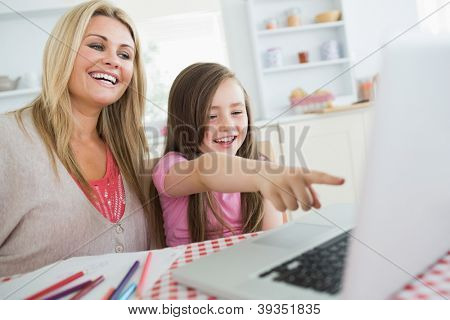 Little girl and mother laughing at laptop at kitchen table