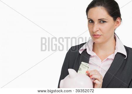 Brunette businesswoman putting dollars into a piggy-bank