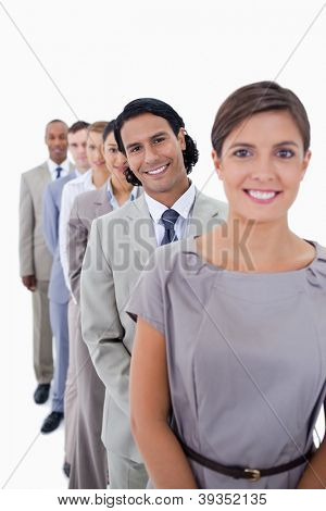Close-up of co-workers in a single line smiling and looking straight with focus on the first man against white background