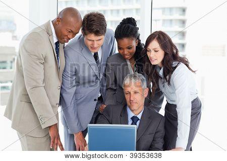 Madura gerente sério dando explicações para a sua equipa atenta com um laptop