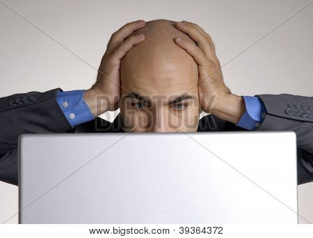 Stressed and confused bald head man working on computer.