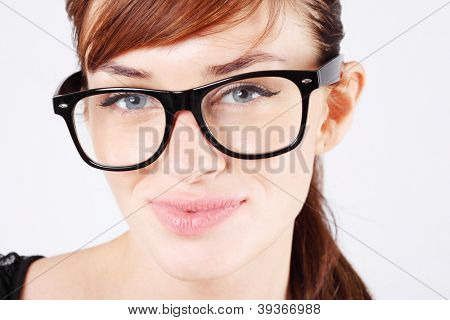 Beautiful woman in big black glasses smiles and looks at camera.