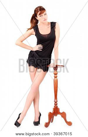 Girl in black stands leaning on tall round table isolated on white background.