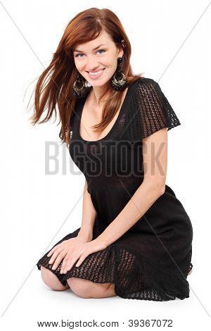 Beautiful girl in black dress and bid earrings sits on floor and smiles isolated on white background.