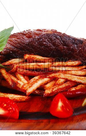 roast steak on potato : fresh grilled beef meat on wood plate with pepper and tomato isolated on white background