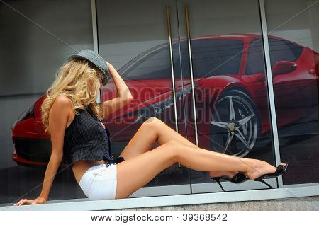Long legs model posing outside with a poster of red car on the background