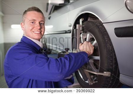 Mechanic repairing a car wheel in a garage