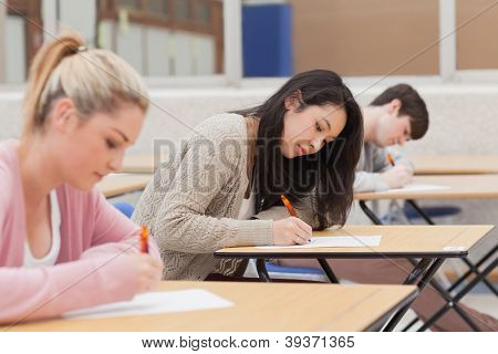 Students taking an exam in exam hall in college