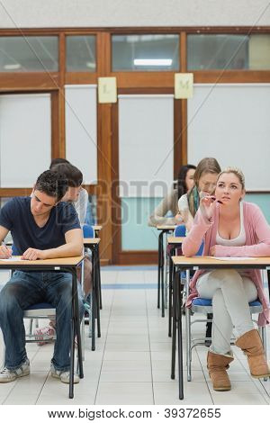 Students in an exam hall while one is thinking in college
