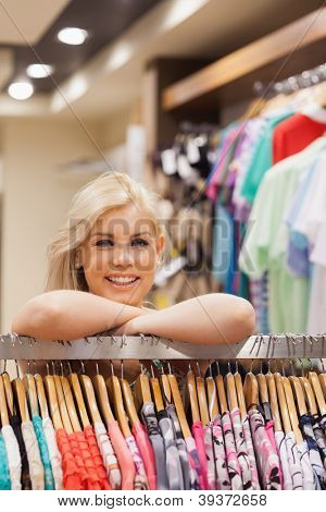 Woman is leaning at a clothes rack of a boutique while smiling