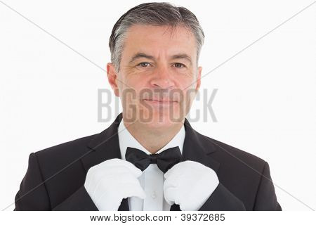 Smiling waiter adjusting his bow tie in front of camera