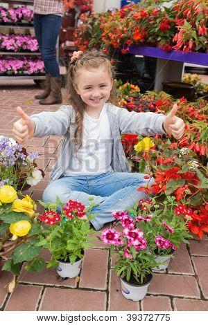 Little girl doing thumbs up sitting on the floor in garden centre