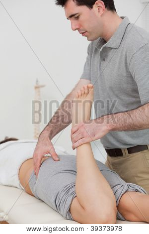 Woman lying while a physiotherapist is bending her leg in a room
