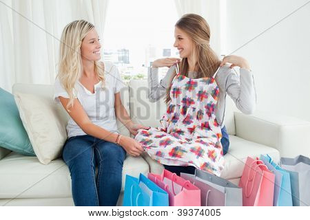 Smiling girls trying out new clothes as they look at one another