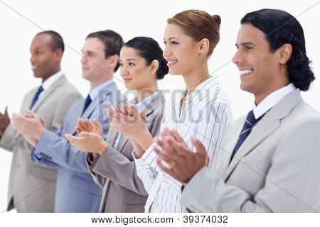 Close-up of business people smiling and applauding with focus on the first three people against white background