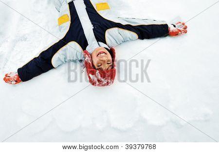 Little boy lies on winter snow