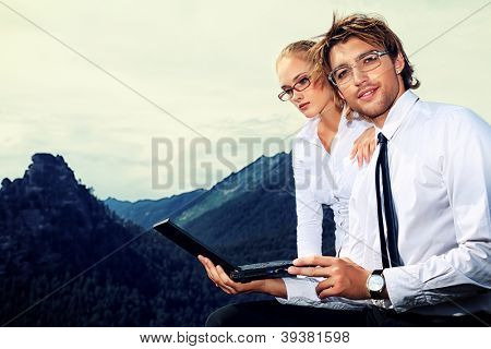 Couple of business people  standing on the top of a mountain with a laptop.