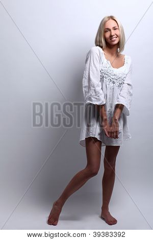 Portrait of shy beautiful blonde dressed in nightgown smiling