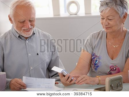 Elderly couple calculating budget, checking bills at home, smiling.