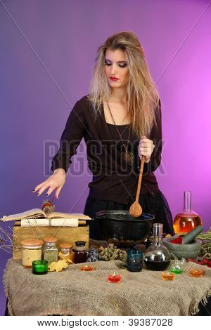 Halloween witch stirring in poison soup in her cauldron on color background