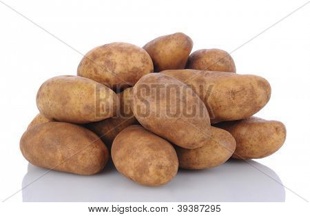 Closeup of a pile of russet potatoes on a white surface with reflection.