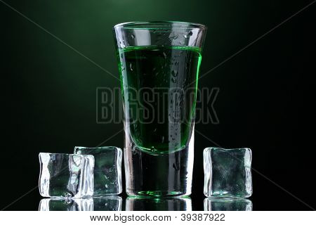 glass of absinthe and ice on green background