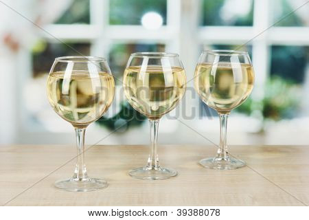 White wine in glass on window background