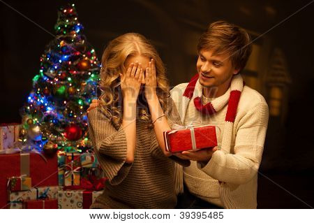 young couple presenting christmas gift