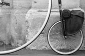 stock photo of penny-farthing  - Old Penny Farthing cycle with a back leather pannier in a historic town of Oamaru - JPG