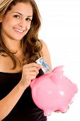 stock photo of save money  - casual woman looking to save money in a piggy bank - JPG