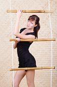 Beautiful young woman in black poses holding bamboo rope ladder.