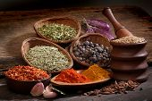 Different spices over a wood background. 	Different spices over a wood background.