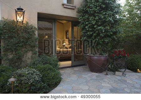 Exterior shot with crazy paving and plants with view into bedroom